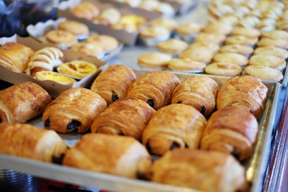 A look inside the display case of a boulangerie. We see pains au chocolat in the foreground, with other, less distinct pastries in the back.