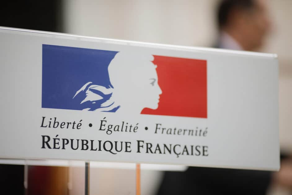 Close-up on a sign showing a common French symbol: the blue, red, and white flag, with the white part being the silhouette of Marianne, the French symbolic female figure. Below, we see the words Liberté, égalité, fraternité and below them in larger letters, République Française.