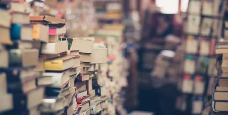Image of a used bookstore, with stacks of books everywhere, and a teetering rotating book display in the background.