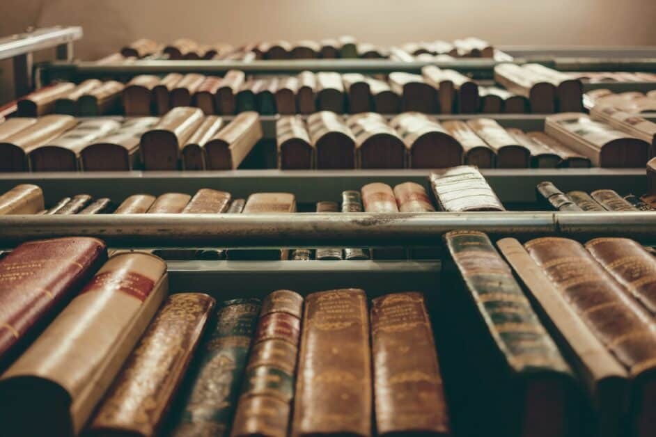 View looking up at a shelf of old leather-bound books