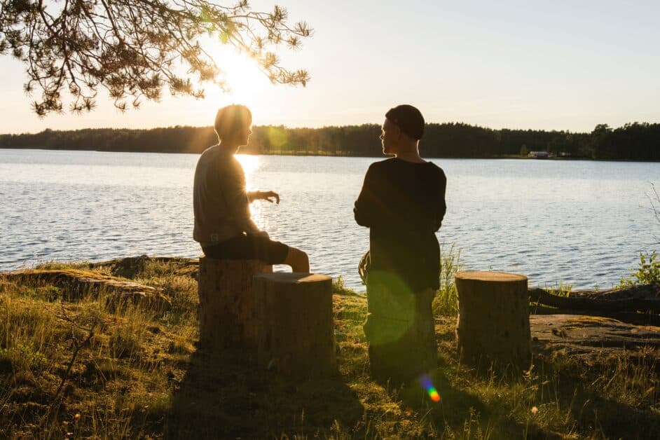 Two men sit on tree stumps on a grassy riverbank, having a conversation. We see them silhouetted by the setting sun.