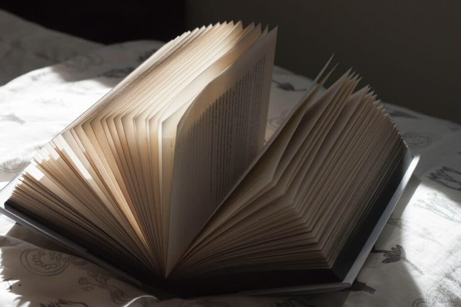 A book is open, its pages standing up, on a sunny spot on a bed in a shadowy room.