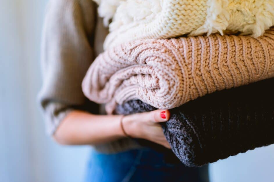 The torso of a woman holding a stack of cozy-looking woven blankets
