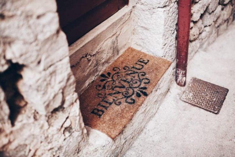 "A welcome mat in a doorway reads ""Bienvenue""."