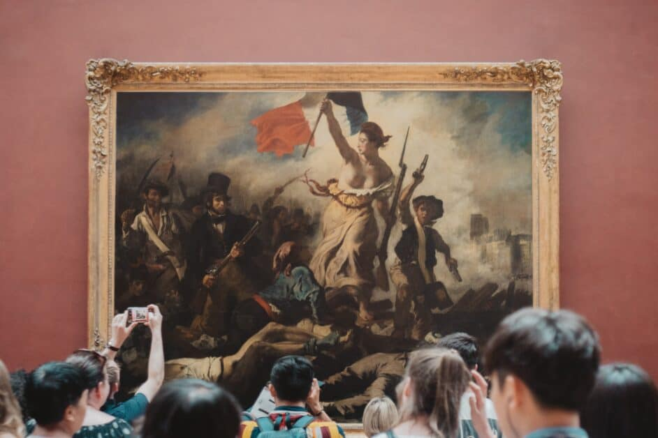 """A crowd of tourists stands in front of Delacroix's """"Liberty Leading the People"""", in the Louvre."""